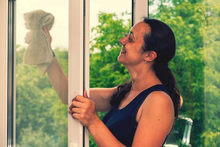 Beautiful woman cleaning window at home. A girl washes windows at home. To clean up the house. Long-haired woman cleaning windows with spray in home. toned