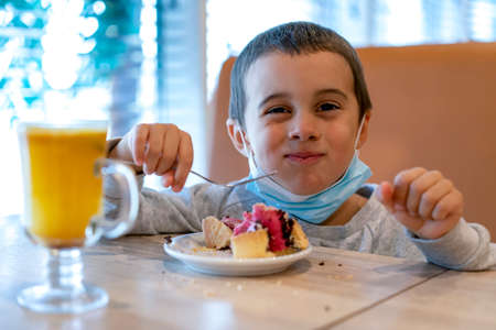 Little boy in a medical mask in a cafe eats a cake. A child wearing a mask in a cafe during a pandemic. selected focus. toned