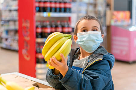 Child wearing surgical face mask buying fruit in supermarket in coronavirus pandemic. little boy in a supermarket is wearing a medical mask. Coronavirus quarantine. toned