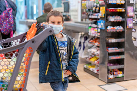 Boy wears protected mask in store. Shopping time during coronavirus outbreak. Boy in a medical mask. Shopping with kids during virus outbreak. Boy in face mask in supermarket. toned