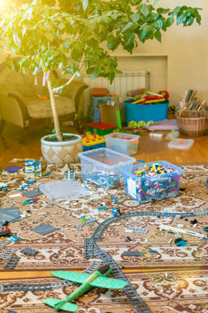 Games floor for preschoolers kindergarten. interior childrens room. mess in the room. mess in the childrens room, scattered toys, boxes on the floor. toned. vertical photo 免版税图像