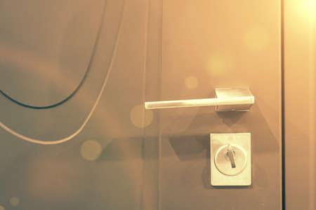 Keys stuck in a lock. closeup Door lock keys, Real estate concept door handle, Key insert and hold in metallic knob on white door horizontal. toned 免版税图像