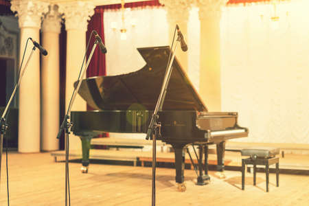 Grand Piano in Concert Hall. Piano standing on empty stage. opened black grand piano with stool on a wooden concert stage. toned Standard-Bild