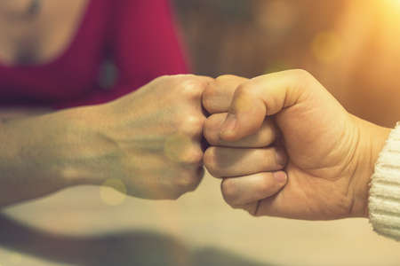 Girl friends greeting on new way in pandemic time. Stop spreading infectious disease touching hand fist. Close up woman and friend doing fist bump. toned