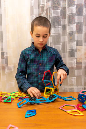 boy playing with magnetic constructor toy. Cute little boy playing with colorful magnetic constructor toy. toned Standard-Bild