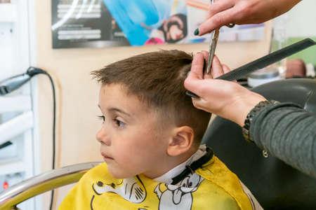 little boy having a haircut at hair salon..Children hairdresser with scissors and comb is cutting little boy. Contented cute preschooler boy getting the haircut