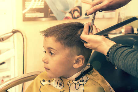 little boy having a haircut at hair salon..Children hairdresser with scissors and comb is cutting little boy. Contented cute preschooler boy getting the haircut. toned