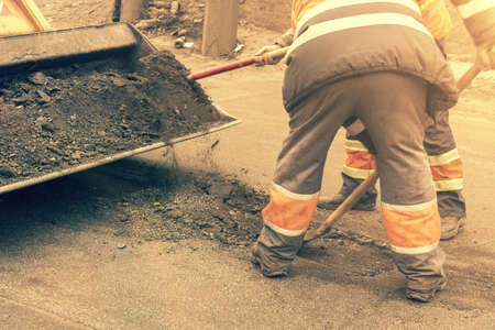 Road workers in bright orange reflective uniforms use shovels to scrape accumulated sand. maintenance of road and highway pavements. pothole repairing works. toned