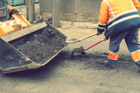 Traffic workers in bright orange reflective uniforms scrape off accumulated sand and debris between lanes with shovels and load it into a metal grader bucket Standard-Bild