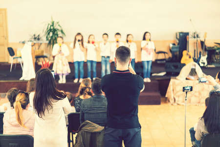Children on the stage. Children on stage perform in front of parents. Young talents on stage. Children stand in front of parents in school. Blurry. toned Standard-Bild