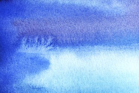 Abstract watercolor background. Texture of blue watercolor. Cobalt granulation. Flowing spots of blue and purple. Gradient shades of blue. Bright ombre ink. Hand drawn background. Horizontal format.