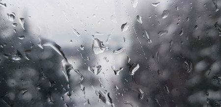 Raindrops on a window with snowy blue mountain landscape outside Stock Photo