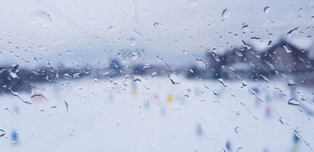 Raindrops on a window with snowy blue mountain landscape outside