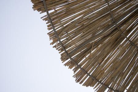 Straw roof of sun umbrella against the blue sky. Stockfoto