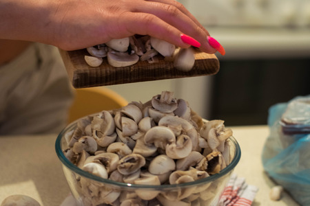 Woman chopping mushrooms with knife on cutting board