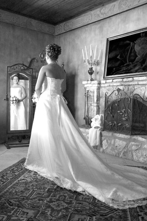 Bride in wedding dress looking at relection in the mirror