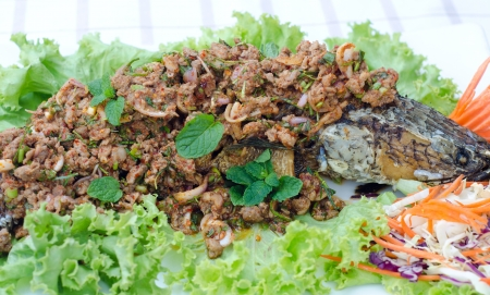 Crispy snake-head fish fried  with spicy salad photo