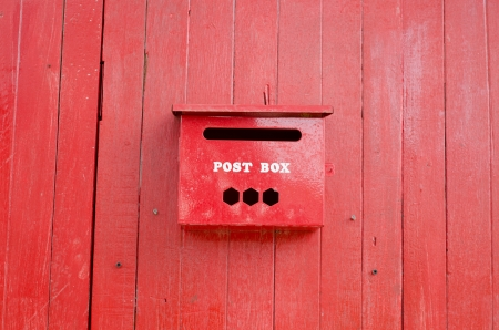 Red post box on wall photo