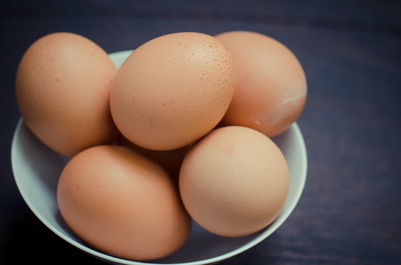 Eggs in bowl on wooden table background photo