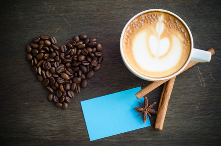 cup of coffee with latte art on wooden background photo