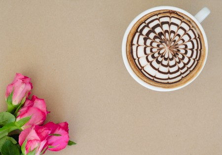 A cup of coffee with latte art and rose on brown paper background photo