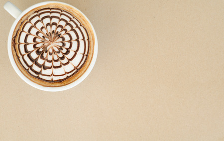 a cup of latte art on brown paper background photo