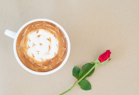 A cup of coffee with latte art and red rose on brown paper background photo