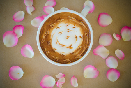cup of coffee with latte art and petal rose on brown paper background photo