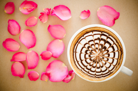 A cup of coffee with latte art and petals rose on brown paper background photo
