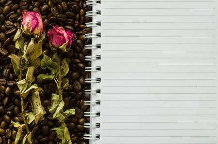 wizened: Notebook and wizened rose on coffee bean background