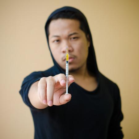 drogadicto: hombre adicto a las drogas con jeringa en la mano