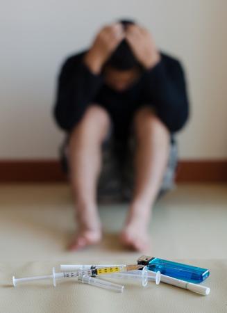 youth crime: syringe and drug addict, sitting in the background Stock Photo