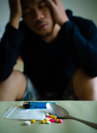droga: drogas y adicto a las drogas, que se sientan en el fondo Foto de archivo