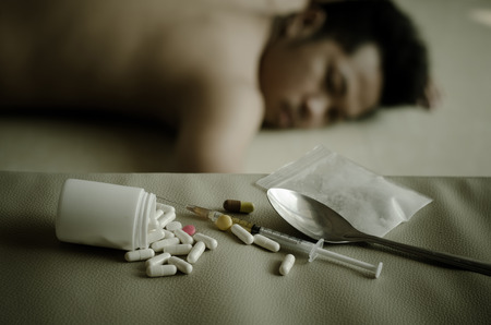 sleeping tablets: drugs and drug addict, laying in the background