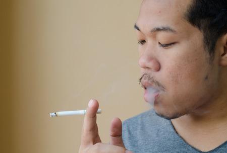 hombre fumando: joven de fumar un cigarrillo