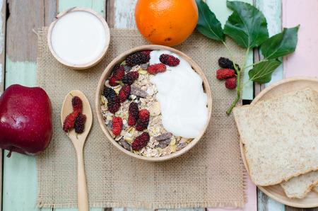 manzana: Desayuno: El hogar hizo el yogur con copos de avena en un taz�n en mesa de madera Foto de archivo
