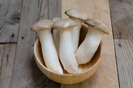 King oyster mushroom Pleurotus eryngii in wooden bowl Stock Photo