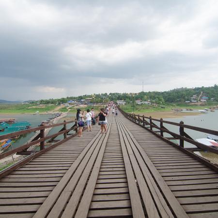 2 way: SANGKLABURI ,THAILAND - MAY 2, 2015 : Traveler crossing wooden bridge or Mon Bridge in Sangklaburi. Kanchanaburi, Thailand. Attractions traditional way of life