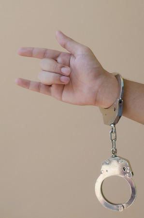 shackle: hand in shackle on brown background