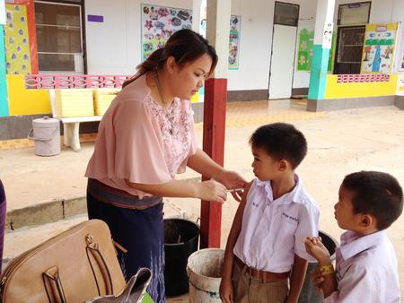 enfermera paciente: Loei, Tailandia-agosto, 28: Las enfermeras son la inyección para proteger contra el sarampión para los niños a nivel primaria en Loei, Tailandia, el 28 de agosto de 2015.It es la política del Ministerio de Salud para prevenir un brote de sarampión en niños tailandeses. Editorial