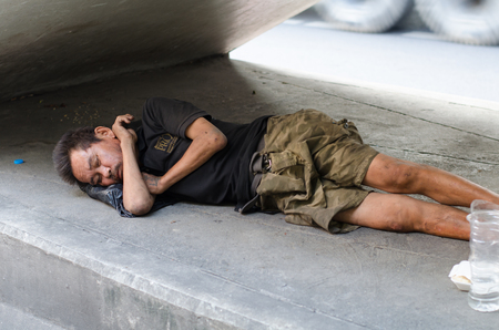 social outcast: BANGKOK, THAILAND - OCTOBER 23, 2015: Homeless man sleeping on the sidewalk. Homelessness is one of the main social issues in Bangkok in Thailand.