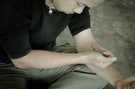 addiction: drug addict man with syringe in action