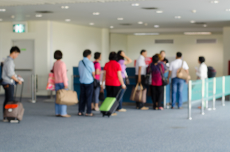 waiting passengers: passengers in row waiting check-in counters at airport on blur background