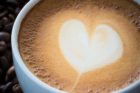 valentine day cup of coffee: close up hot coffee with foam milk art pattern