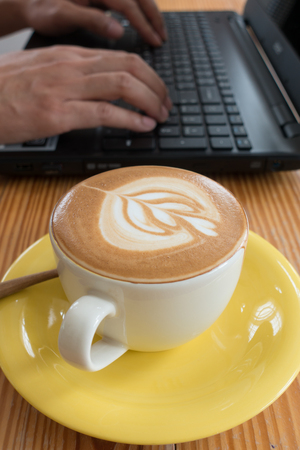 Latte coffee with laptop on old wooden table Stock Photo