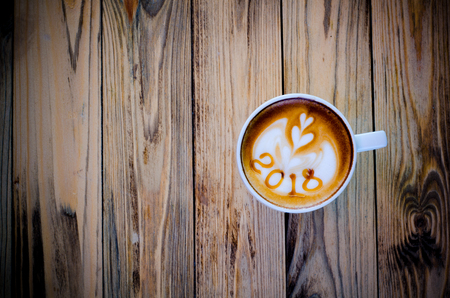 hot coffee with foam milk art 2018 on wooden table