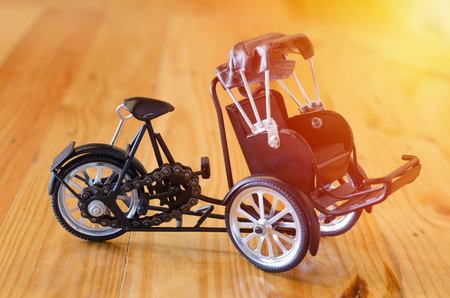 three wheeler: Small wooden toy, three - wheeler tricycle taxi model on wooden background Stock Photo