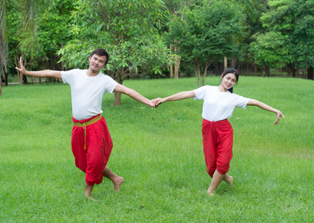 Asian young boy and girls learning Thai dance. Classical Dance in white shirt red loincloth, Demonstrate dance in the garden