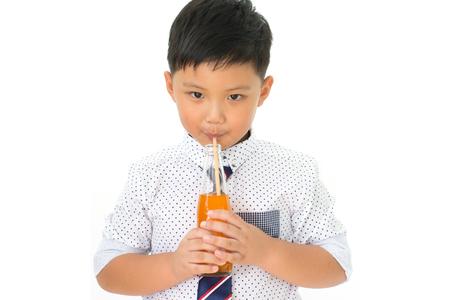 Portrait of little boy drinking fresh orange juice isolated on white background
