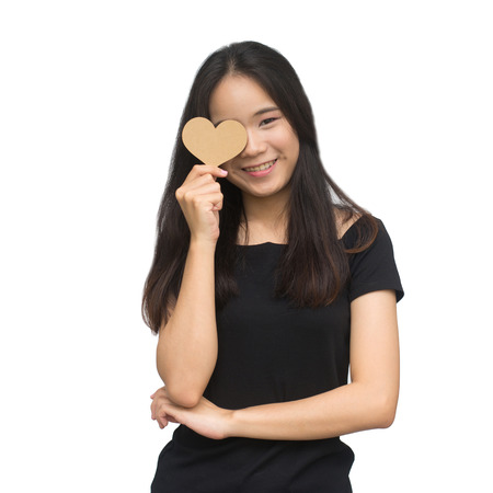 Beautiful asian young girl holding brown love heart over eye isolated on white background with cliipping Path